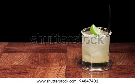 margarita on the rocks on a bar top isolated on a black background - stock photo