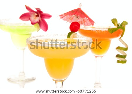 Margaritas cocktails composition decorated with lime, orchid, cherry and cocktail umbrella isolated on a white background