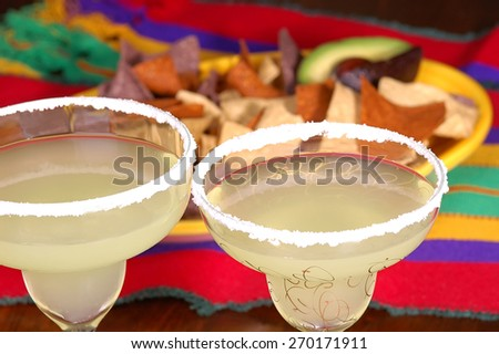Margaritas with platter of corn chips on Mexican table cloth. Ready for a Cinco de Mayo project. - stock photo
