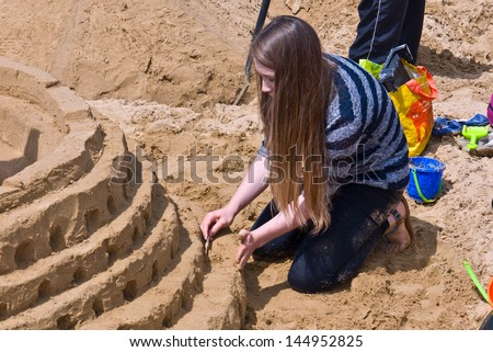 MARGATE, UK-JUNE 29: Team member working on their Colosseum sand castle in the RIBA sandcastle Challenge, on Margate's main sands watched by many visitors to the beach. June 29, 2013 Margate UK - stock photo