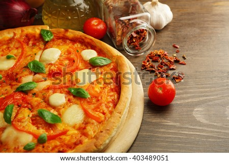 Margherita pizza with tomatoes and spices on wooden background