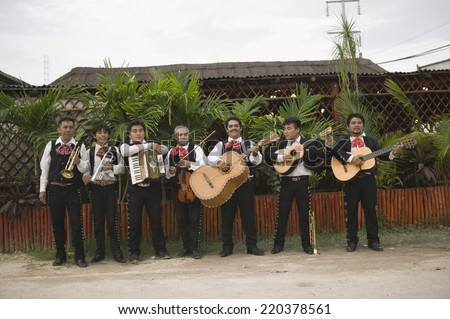 Mariachi band in front of building playing their instruments - stock photo