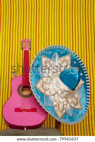 mariachi embroidered sombrero and pink guitar in striped mexican background - stock photo