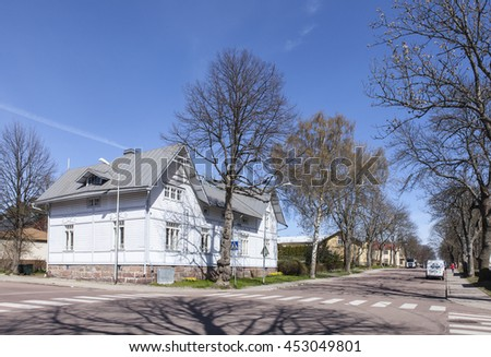 MARIEHAMN, ALAND ON MAY 07. View of a small town by the sea on May 07, 2016 in Mariehamn, Aland. Wooden buildings along a street with trees and gardens.