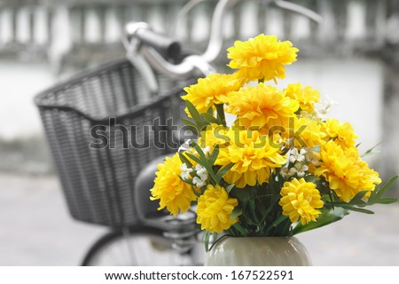 Marigold flower and old bicycle on street - stock photo