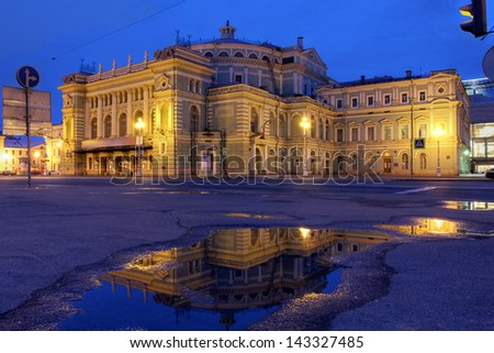 Mariinsky Theatre and Opera House in Saint Petersburg, Russia surprised during the twilight of the June's white nights while reflection in a small rain pond. - stock photo