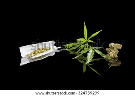 Marijuana background. Cannabis cigarette joint, bud and hemp leaves isolated on black background. Addictive drug or alternative medicine.  - stock photo