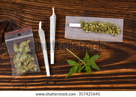 Marijuana background. Cannabis joint, bud in plastic bag and hemp leaves on wooden table. Addictive drug or alternative medicine.  - stock photo