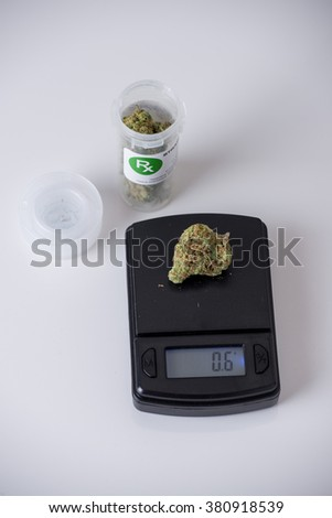 marijuana bud being weighed on a digital scale - stock photo