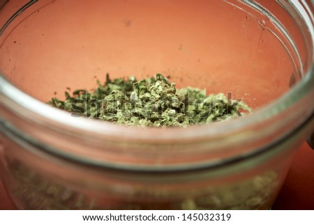 Marijuana in Jar, Red Background  - stock photo