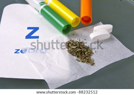 marijuana in paper with crayons in background