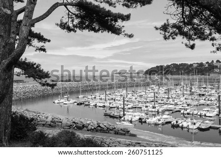Marina of Trebeurden at Pink Granite Coast (Brittany, France). Aged photo. Black and white.