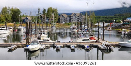Marina. Pacific ocean bay. Pier of the ships, yachts and boats. Foggy mountains and green forest landscape.Tofino. British Columbia. Canada