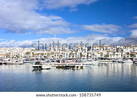 Marina waterfront with luxury motor yachts in holiday resort town of Puerto Banus on Costa del Sol, near Marbella in Spain, Malaga province. - stock photo