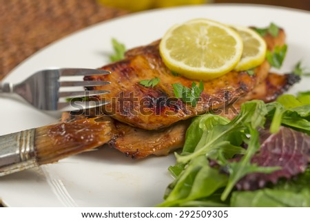 Marinated and grilled chicken breast with lemon and salad greens