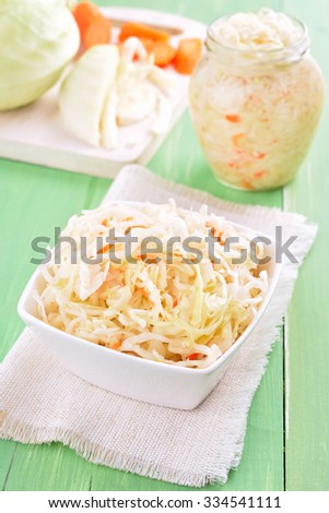 Marinated cabbage (sauerkraut) on wooden green table - stock photo