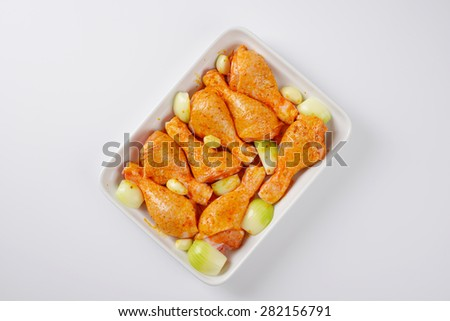 marinated chicken legs in white ceramic baking tin - stock photo