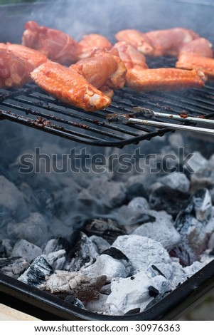 Marinated chicken over the coal on the barbecue stand