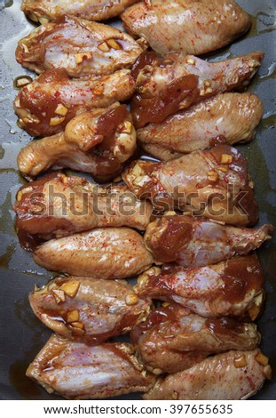 Marinated chicken wings on a black pan. - stock photo