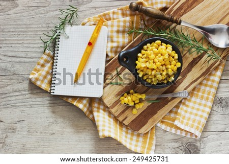 marinated corn in a bowl on a cutting board and rosemary on a wooden background. home preservation. top view.  home cooking concept - stock photo