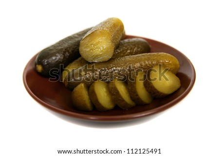 Marinated cucumbers on the plate isolated on white - stock photo