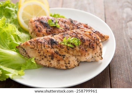 Marinated grilled chicken breasts cooked BBQ and served with fresh herbs and lemon. - stock photo