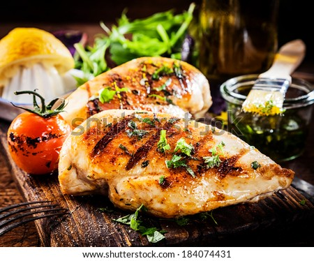 Marinated grilled healthy chicken breasts cooked on a summer BBQ and served with fresh herbs and lemon juice on a wooden board, close up view - stock photo