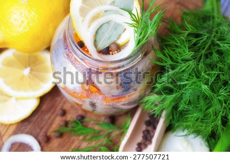 Marinated herring in a jar with vegetables and herbs - stock photo