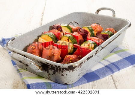 marinated hungarian pork and vegetable skewers in a rustic roasting tray - stock photo