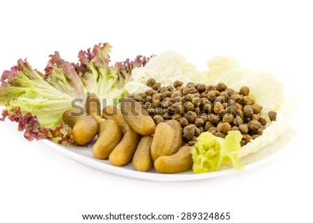 Marinated pickled cucumbers, capers and lettuce on plate. - stock photo