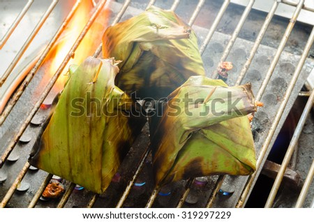 Marinated pork in banana leaf grill on fire, thai style