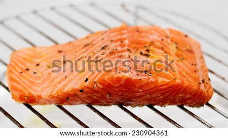Marinated salmon fillet on grill, soft focus - stock photo