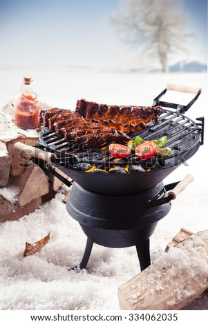 Marinated spare ribs and colorful vegetables cooking on a winter barbecue outdoors in a snowy landscape - stock photo