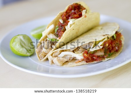 Marinated striped bass tacos with cabbage slaw, and fresh salsa. - stock photo