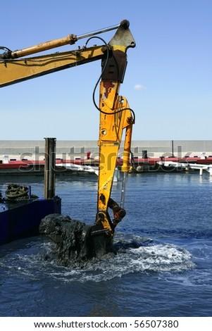 marine dredging digging sea bottom black mud in marina - stock photo