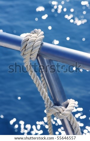 marine knot detail on stainless steel boat railing banister - stock photo