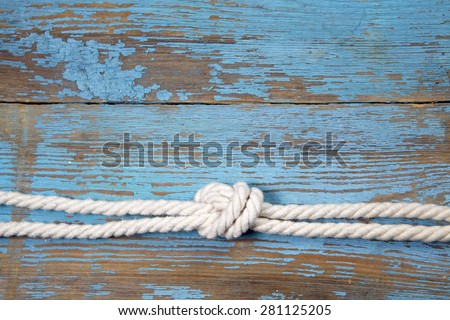 Marine knot on blue wooden background - stock photo