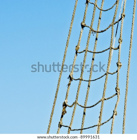 Marine rope ladder at pirate ship. Sea hemp ropes on the old nautical vessel. Ladder upstairs on the mast. - stock photo