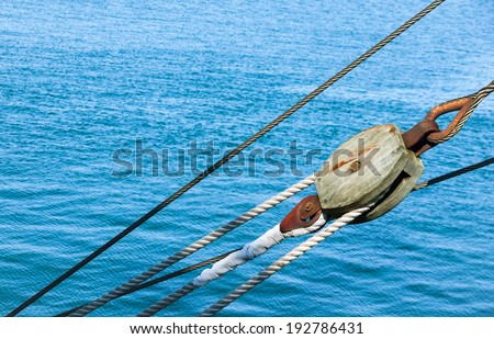 Marine ropes and tackles on the tall ship from sea journey. Old wooden block with rope on the sail. Marine pulley closeup on the old vessel. - stock photo