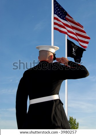 Marine saluting with American and POW flag - stock photo