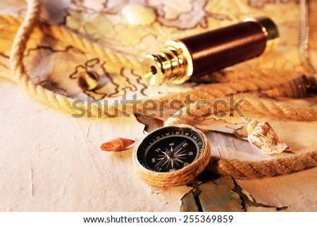 Marine still life spyglass and world map on old wooden background - stock photo