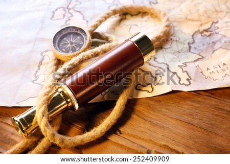 Marine still life spyglass, compass, rope and world map on wooden background - stock photo
