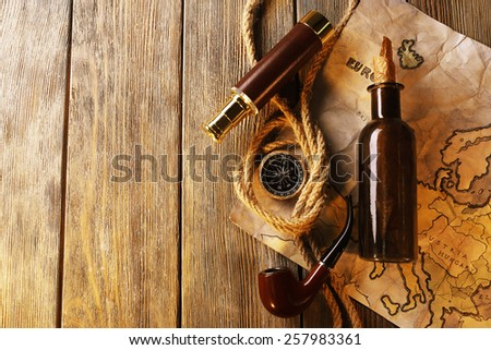 Marine still life spyglass, rope, pipe and world map on wooden background - stock photo