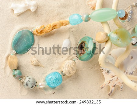 Marine style necklace lying on white sand - stock photo