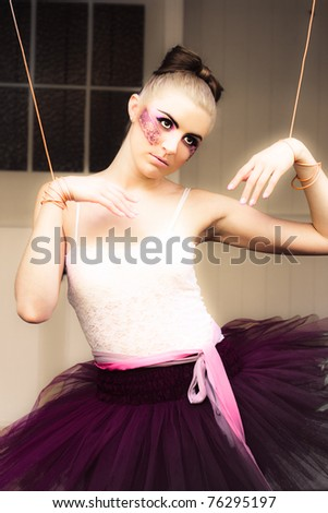 Marionette Doll Wearing Tutu Or Leotard Hanging Or Suspended On Strings And Cords In A Artistic Representation Of Management Dominance Control And Power - stock photo