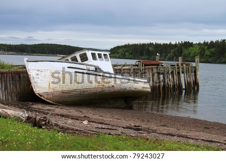 Maritime beached and old fishing boat leaning on a wooden pier on the shores of the Bay of Fundy in Maces Bay, New Brunswick, Canada