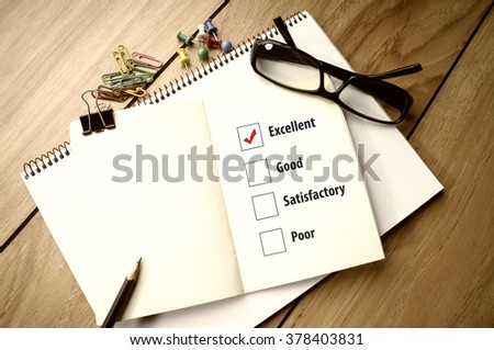 Mark Excellent: Ticked checkbox evaluation form and pencil on notebook - stock photo