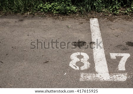 Mark that splits parking spot number eight by seven with a few oil stains on the asphalt - stock photo