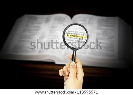 marked phrase in Holy Bible under magnifying glass - stock photo