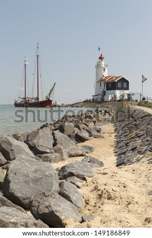 "MARKEN - JULY 15: An old wooden sailboat visits the ""Paard van Marken"" lighthouse in Marken, the Netherlands, on July 15, 2013."